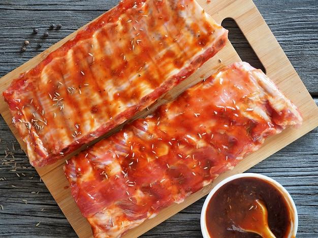 Żeberka w pomidorowym sosie barbecue. surowe mięso przygotowane do pieczenia. widok z góry.