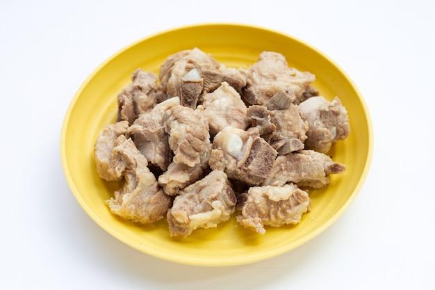 Żeberka wieprzowe gotowane w żółtym talerzu na białym tle.