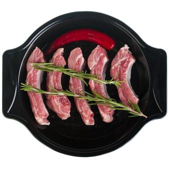 Żeberka wieprzowe w naczyniu do pieczenia z rozmarynem i ostrą papryką, na białym talerzu, odizolować