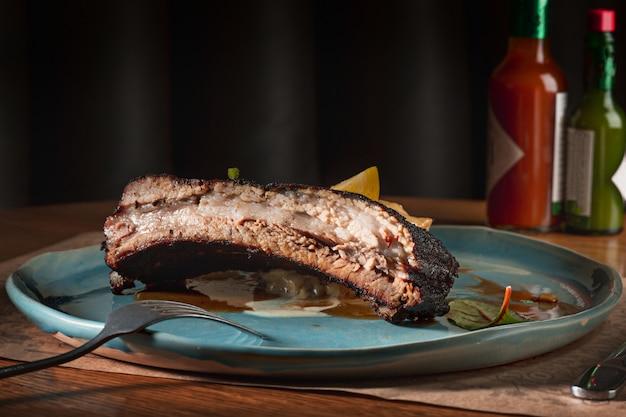Żeberka wieprzowe z grilla na ciemnym talerzu na drewnianym stole