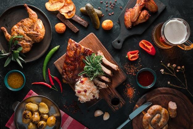 Żeberka wieprzowe z grilla z kiełbasą, kurczakiem i ziemniakami na łupku czarnym tle z kuflem piwa. widok z góry na płasko