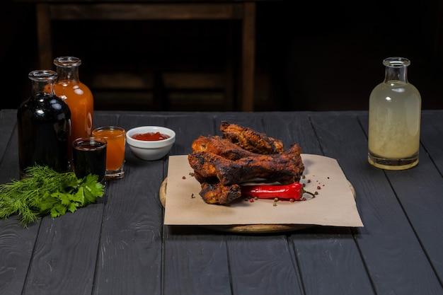 Żeberka z grilla i sos pomidorowy na czarnym tle drewnianych