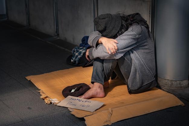 Żebracy, bezdomni siedzą na podłodze.
