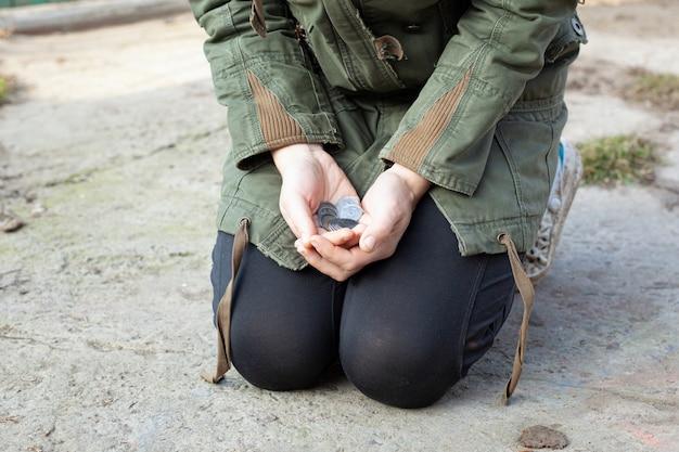 Żebrak prosi o pieniądze przechodniów. mała rzecz w rękach biednych.