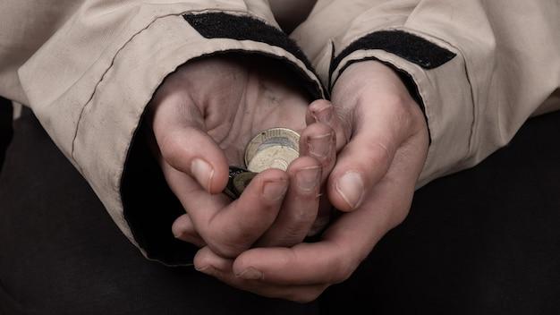Żebrak z brudnymi rękami błagający o pieniądze, prośba o pomoc finansową.