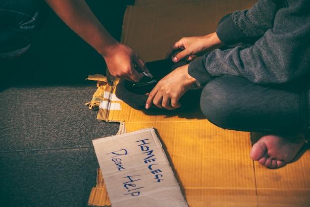 Żebraki, bezdomni siedzący na podłodze.