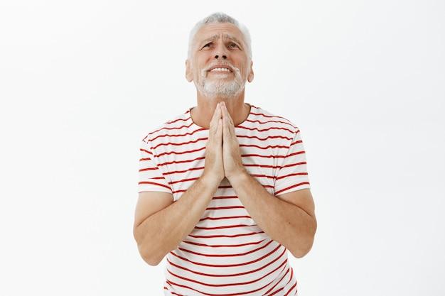 Żebranie starszego mężczyzny, błagającego boga, błagającego