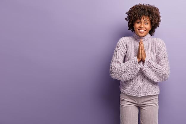 Żebrząca urocza afroamerykańska dama ma błagalną pogodną twarz, prosi o wsparcie, trzyma dłonie w modlitewnym geście, nosi swobodny zimowy sweter, odizolowany od fioletowej ściany.