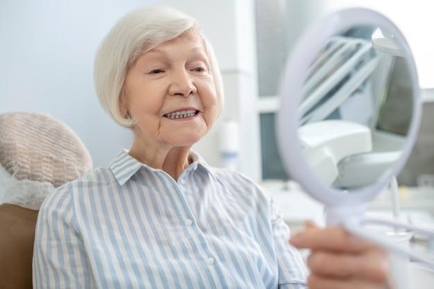 Zęby po odbudowie. starsza kobieta siedzi w gabinecie dentystycznym i patrzy w lustro po odbudowie zębów