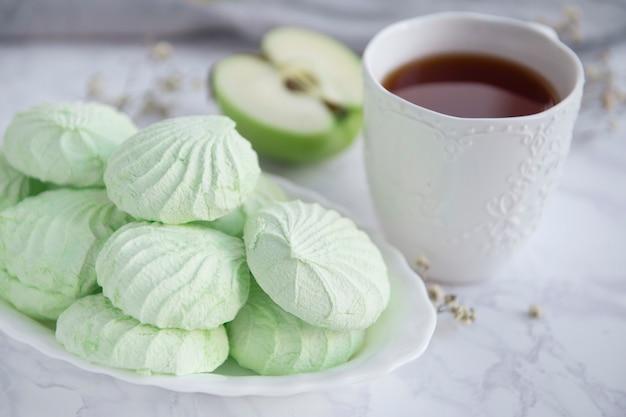 Zefir jabłkowy i białe filiżanka herbaty z bliska