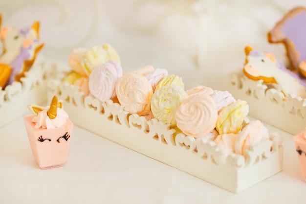 Zefir pastelowych tonów na białej podstawce i różowego mini tortu w formie jednorożca