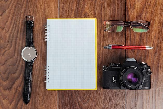 Zegar, aparat i notebook na brązowym
