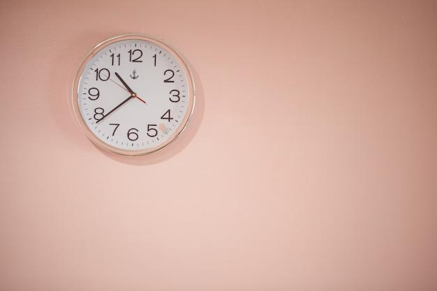 Zegar biały na różowym tle.