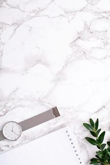 Zegar, biały notatnik i zielenie na marmurze