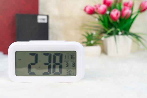 Zegar cyfrowy z książką ozdobiony na stole