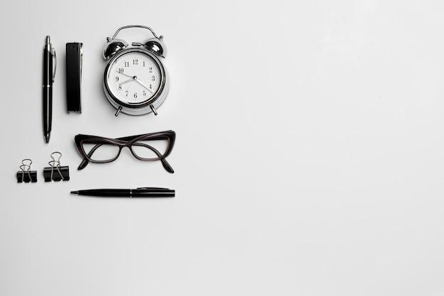 Zegar, długopis i okulary na białym tle