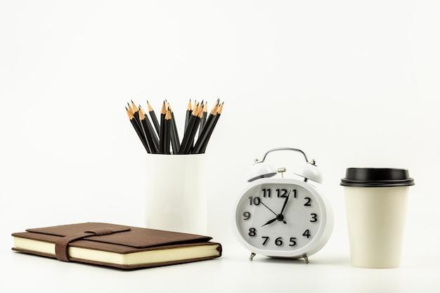 Zegar, filiżanka, ołówek i rzemienny notatnik na białym biurka tle z kopii przestrzenią