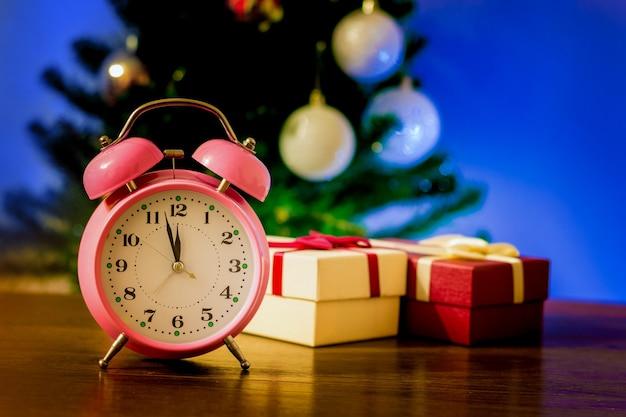 Zegar i pudełka z prezentami pod choinką_