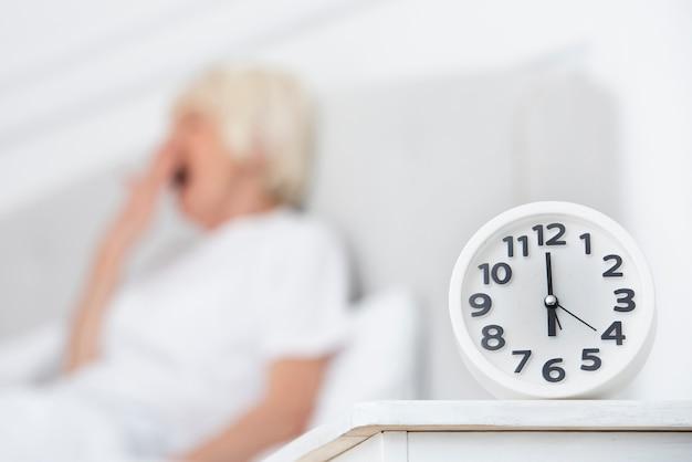 Zegar i starsza kobieta na zamazanym tle