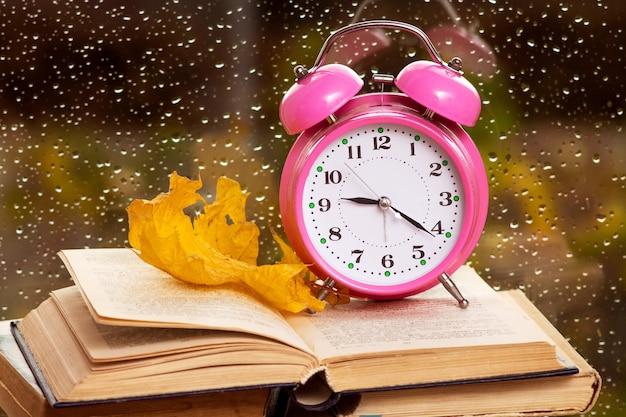 Zegar i suchy liść klonu na książce na tle okna w deszczową pogodę jesienią wieczorem.