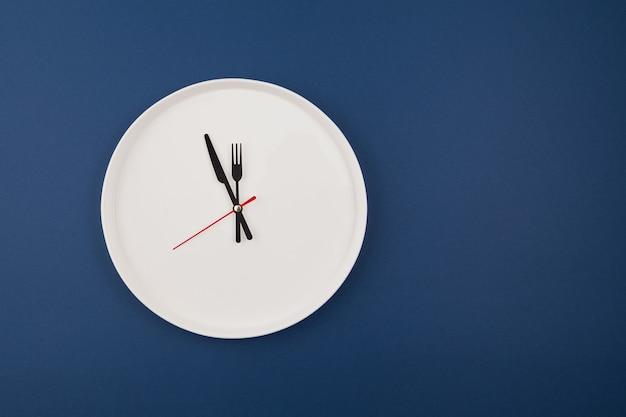 Zegar na białym talerzu na niebiesko