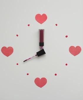 Zegar na białym tle wykonany z produktów kosmetycznych do makijażu, szminki i pędzla.