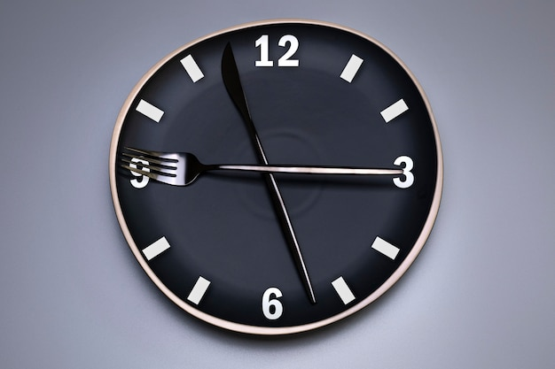 Zegar na czarnym talerzu, ze sztućcami, szare tło. pojęcie okresowego postu, lunchu, diety i utraty wagi. czas na dietę.