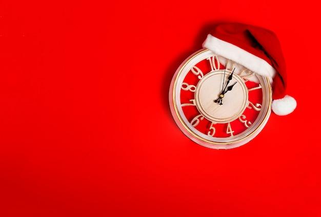 Zegar na czerwonym tle w kapeluszu świętego mikołaja