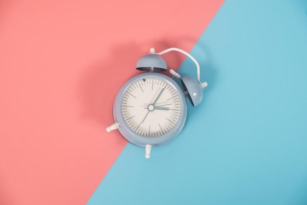 Zegar na kolorowym tle z miejsca na kopię. płaskie lay nowoczesne i minimalny styl.
