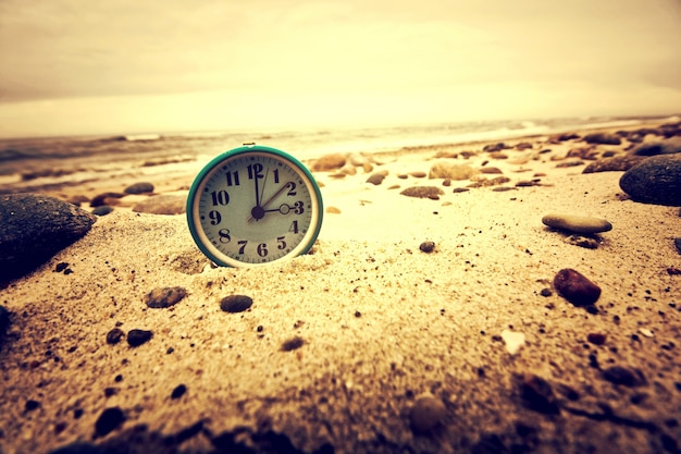 Zegar na plaży. czas i koncepcji.