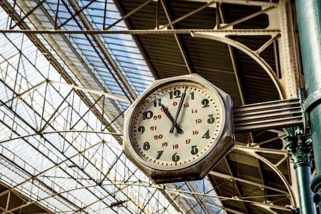 Zegar na stacji kolejowej, duży stary, zabytkowy zegar wiszący na dachu dworca kolejowego