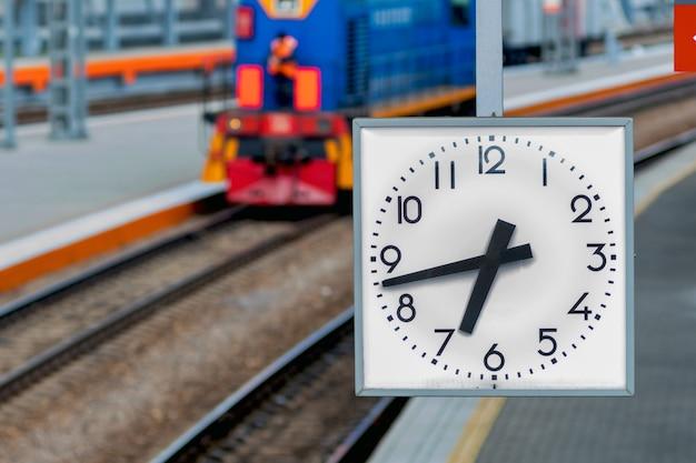 Zegar na stacji kolejowej. zegar wskazujący czas odjazdu pociągów. pociąg jedzie koleją