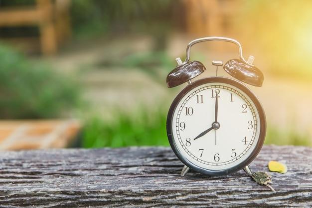 Zegar na stole z drewna z czasem zielonym tle przyrody o 8 rano