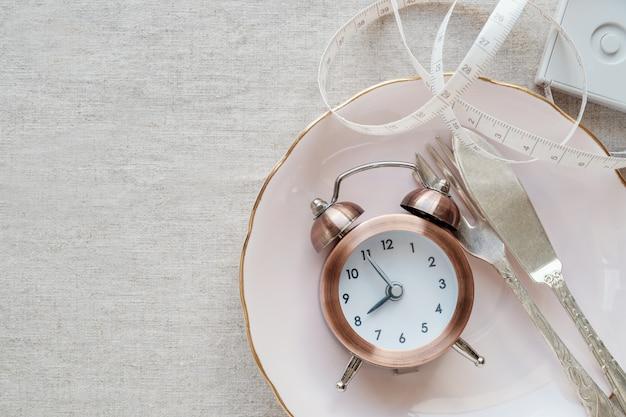Zegar na talerzu i centymetrze, przerywana koncepcja diety na czczo