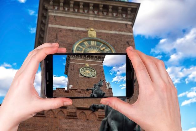 Zegar na wieży ratusza na głównym placu w krakowie z bliska, polska. turysta robi zdjęcie