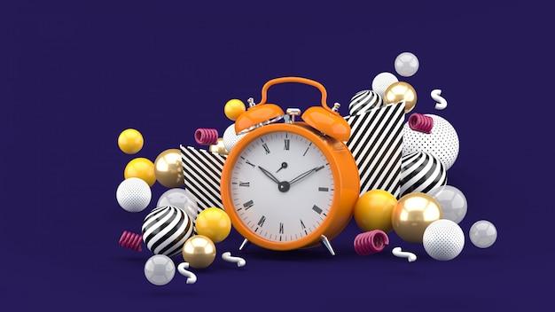 Zegar otoczony kolorowymi kulkami na fioletowej przestrzeni