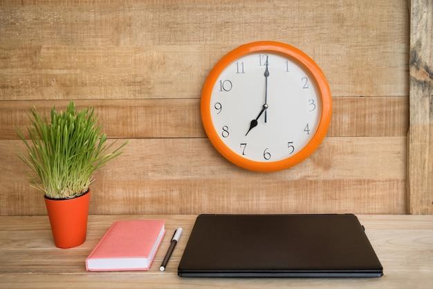 Zegar ścienny, laptop, notatnik i długopis. domowe miejsce pracy. zielona roślina doniczkowa na stole. drewniany .