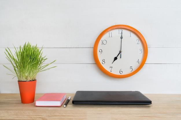 Zegar ścienny, laptop, notatnik i długopis. domowe miejsce pracy. zielona roślina doniczkowa na stole.
