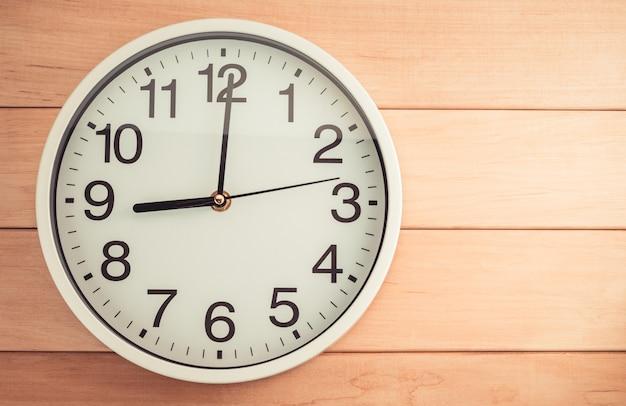 Zegar ścienny na drewnianym stole