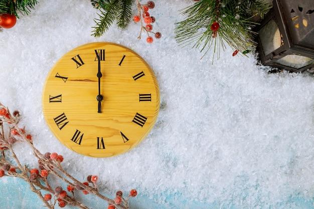 Zegar w stylu drewna odliczający do północy odlicza ostatnie chwile przed nowym rokiem z szyszkami, płatkami śniegu i kulą bożonarodzeniową latarnią
