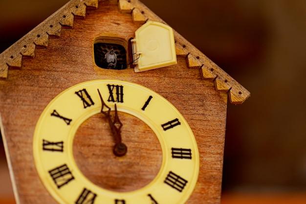 Zegar w stylu retro z kukułką i cyframi rzymskimi. niedługo na tarczy pojawi się godzina dwunasta. ścieśniać.