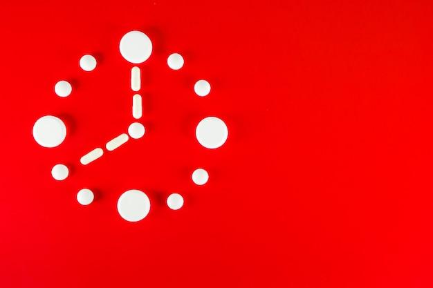 Zegar wykonany z białych tabletek na czerwonym tle, widok z góry.