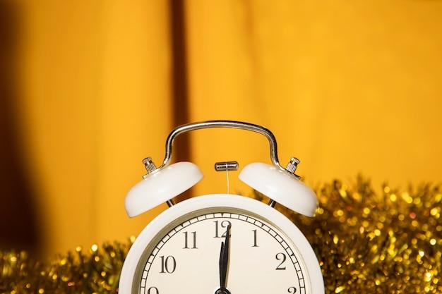 Zegar z bliska ze złotymi dekoracjami z tyłu