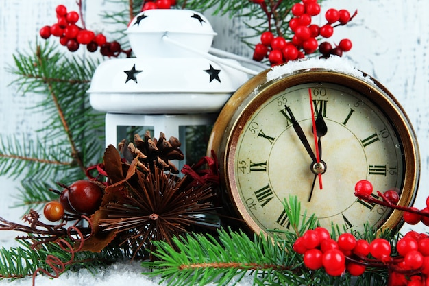 Zegar z gałęzi jodłowych i ozdób choinkowych na stole na drewnianym tle