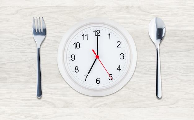 Zegar z naczyniami na czystym tle drewna, skład płaskiej świeckich