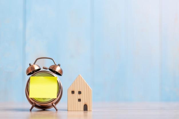 Zegar z notatką papierową i model domu na drewnie