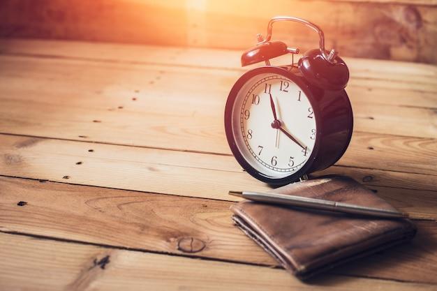 Zegar z portflem i piórem na drewnianym tle
