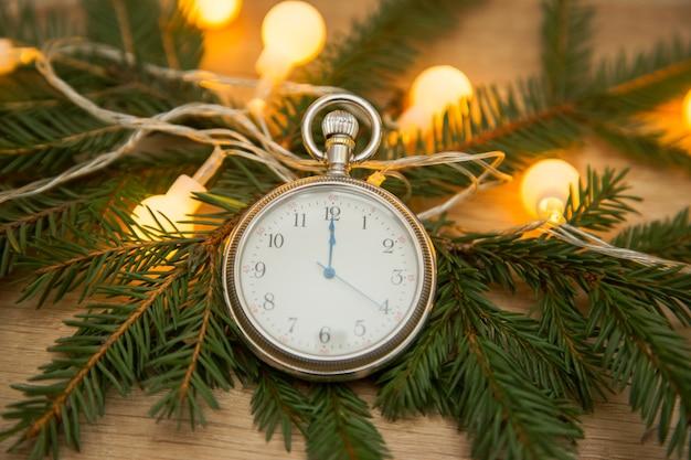 Zegar ze strzałkami o północy z gałęziami jodły. nowy rok