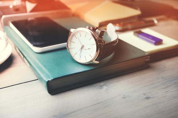 Zegarek i telefon na książce, filiżanka kawy na drewnianym stole