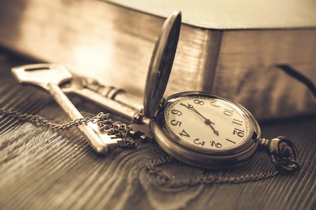 Zegarek kieszonkowy i stara książka ze stronami